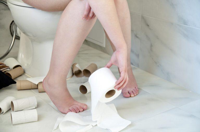 Человек на унитазе с туалетной бумагой в руках