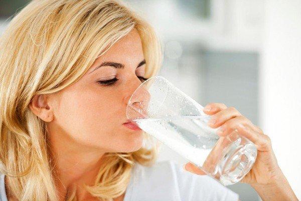 Девушка пьёт воду из стакана