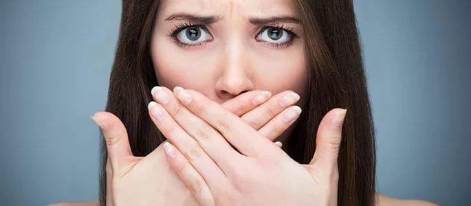 Женщина закрывает рот руками